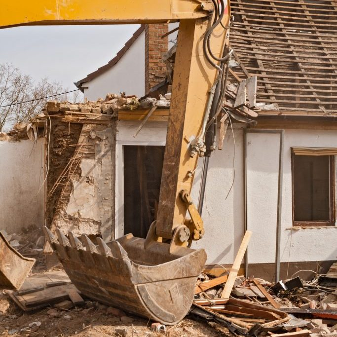 A large track hoe excavator tearing down an old house