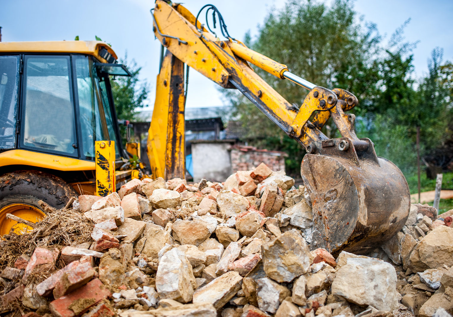 industrial hydraulic excavator on construction and demolition site recycling construction waste with bulldozer
