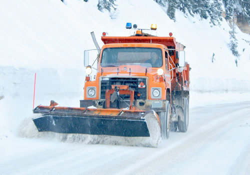 Snow plow removing snow from mountain highway